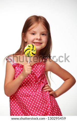 Cheerful little girl in a summer dress eating a large yellow lollipop - stock photo
