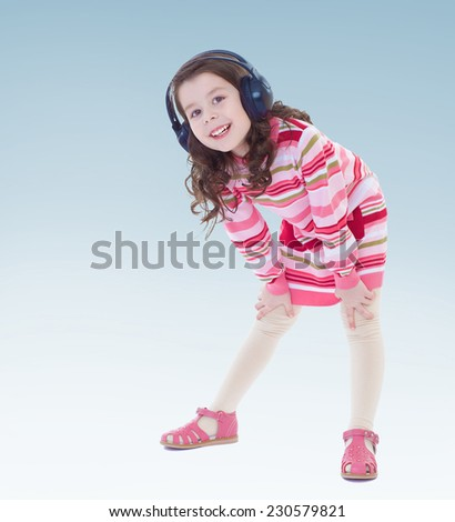 Cheerful little girl in big black headphones. - stock photo