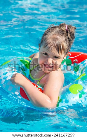 Cheerful little girl in the outdoor pool - stock photo