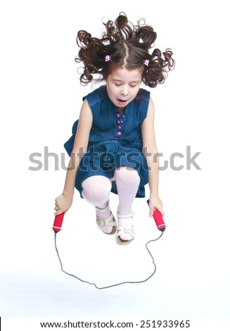 Cheerful little girl jumping on a skipping rope.Isolated on white background, Lotus Children's Center. - stock photo