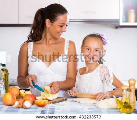 Cheerful little girl learning recipe of yeasty dough for bread indoors - stock photo