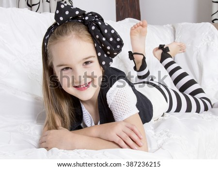 cheerful little girl looking up with a smile - stock photo