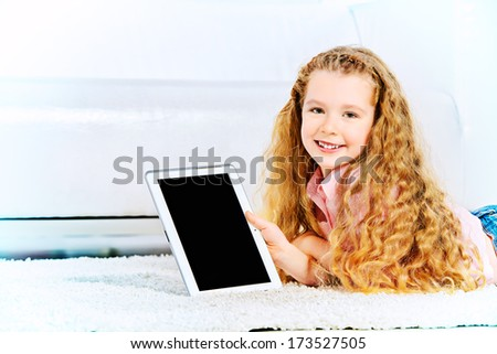 Cheerful little girl lying on a carpet at home and playing with a digital tablet. - stock photo