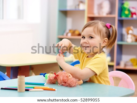 Cheerful little girl play in preschool, shallow DOF - stock photo