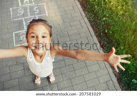 cheerful little girl playing hopscotch on playground outside  - stock photo
