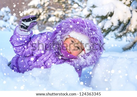 Cheerful little girl playing in a snowy forest. On the face of snowflakes and a drop of water from melting snow. - stock photo