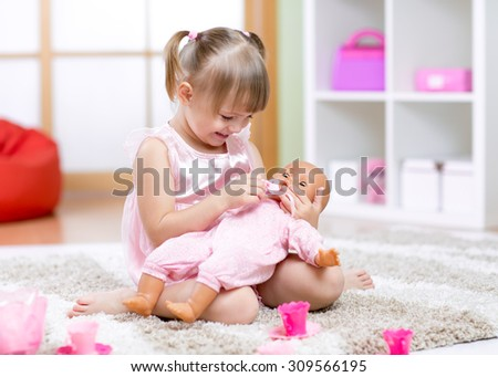 Cheerful little girl playing with doll in preschool