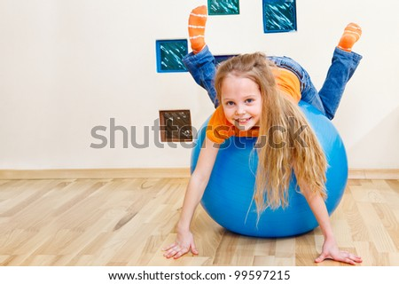 Cheerful little girl playing with gymnastic ball - stock photo