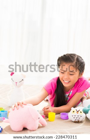 Cheerful little girl playing with knitted toys  - stock photo