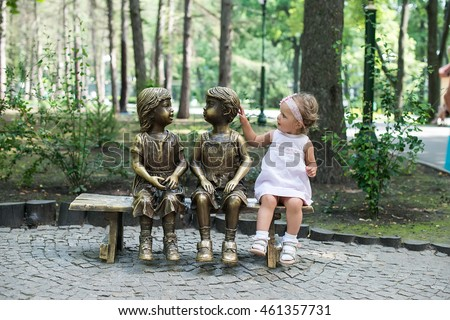 cheerful little girl playing with park statues. Summer holiday outdoor and communication concept