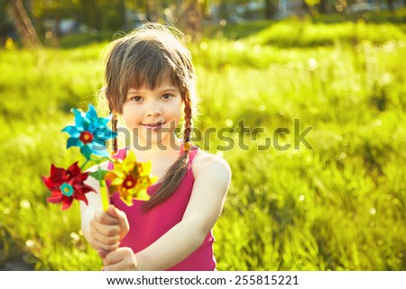 cheerful little girl playing with pinwheel in the park on a green background - stock photo