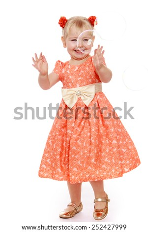Cheerful little girl playing with soap bubbles. - stock photo