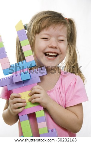 Cheerful little girl playing with toy -  plastic blocks