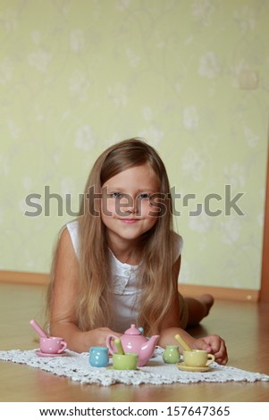 Cheerful little girl playing with toys in her room/Girl playing with a set of children's dishes - stock photo