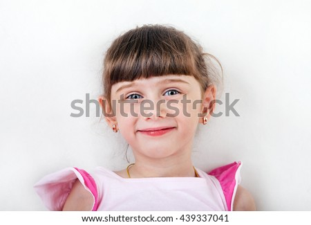 Cheerful Little Girl Portrait on the White Wall Background - stock photo