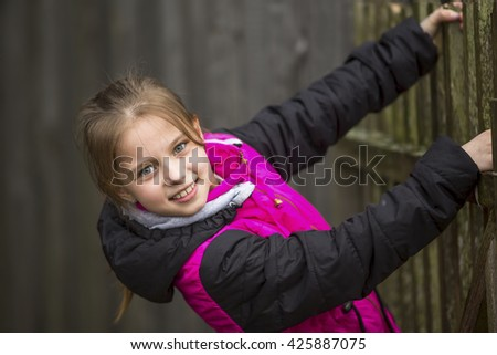 Cheerful little girl portrait while playing outdoors. - stock photo