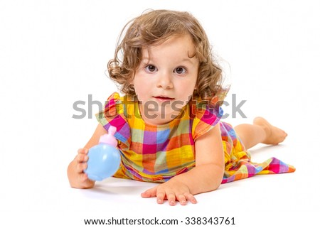 Cheerful little girl smiling at camera lying on white background.
