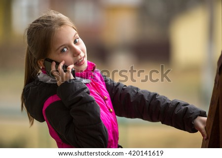 Cheerful little girl talking on a mobile phone call. - stock photo