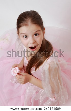 Cheerful little girl wearing pink dress as a princess - stock photo
