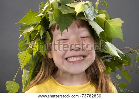 Cheerful little girl with a wreath on a head from birch leaves on a gray background - stock photo