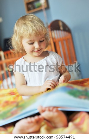 cheerful little girl with book sits on bed of parents - stock photo