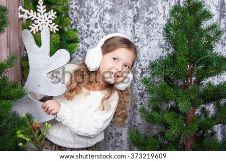 Cheerful little girl with ear muffs in her head playfully peeking out from behind trees - stock photo