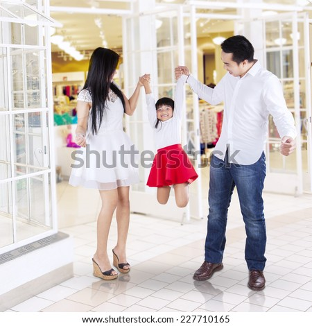 Cheerful little girl with her parents playing together in the mall - stock photo