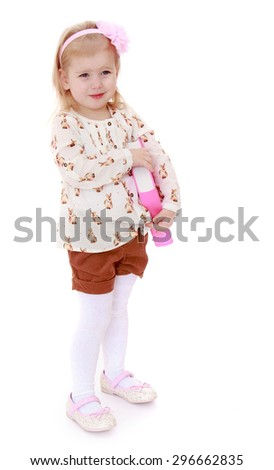 Cheerful little girl with short blond hair who is holding a pink headband in a bright silk shirt and brown shorts , holding under his arm a thick book - isolated on white background - stock photo