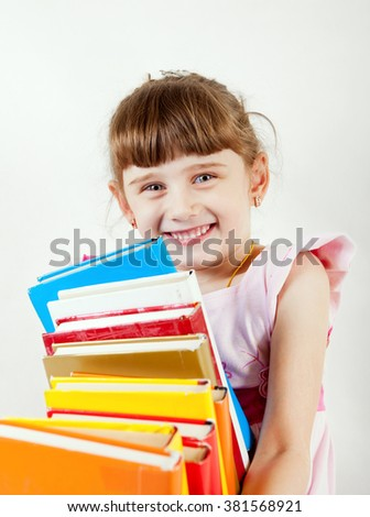 Cheerful Little Girl with the Books on the White Wall Background - stock photo