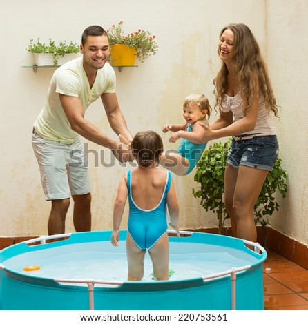 Cheerful little girls and laughing parents having fun in pool at terrace - stock photo