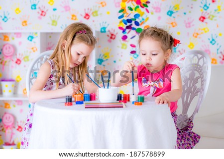 Cheerful little girls with water colors  drawing in kindergarten - stock photo