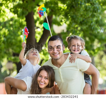 Cheerful little girls with windmills sitting on smiling parent's arms outdoor