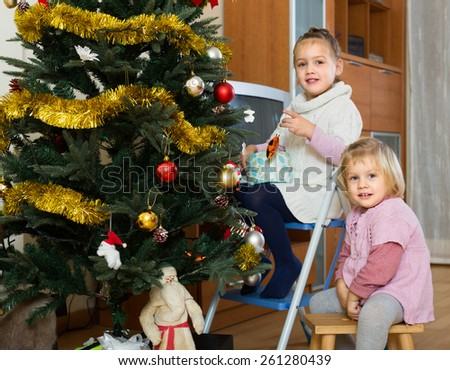 Cheerful little sisters decorating Christmas tree at home. Selective focus on one girl