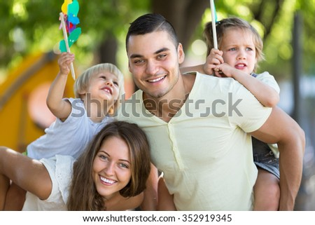 Cheerful little sisters with windmills sitting on smiling parent's arms outdoor. Focus on man