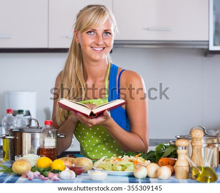 Cheerful long-haired american blondie preparing veggies in domestic kitchen  - stock photo