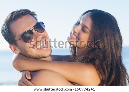 Cheerful loving couple hugging each other on the beach - stock photo