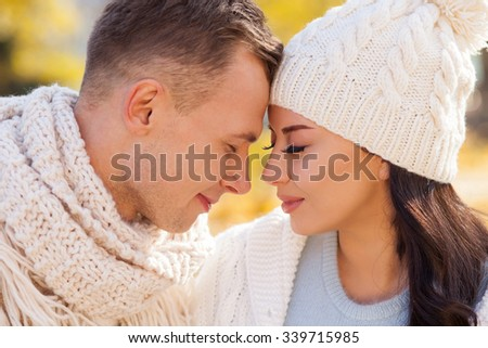 Cheerful loving couple is dating in the autumn park. They are sitting near each other and gently smiling. The man and woman are closed their eyes with pleasure - stock photo