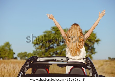 Cheerful loving couple is traveling by car with joy. The man is sitting at steering wheel with joy. The woman is standing and raising her hands up with enjoyment - stock photo