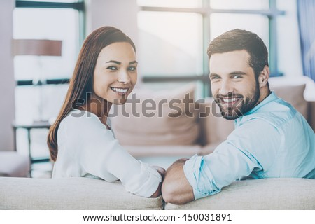 Cheerful loving couple. Rear view of beautiful young loving couple sitting together on the couch and smiling - stock photo