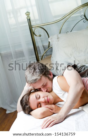 Cheerful loving couple relaxing on bed