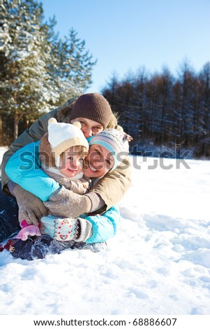 Cheerful loving family sit embracing in the winter park - stock photo