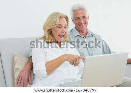 Cheerful loving senior couple using laptop on sofa in a house