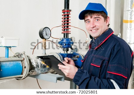 cheerful maintenance engineer checking technical data of heating system equipment in a boiler room - stock photo