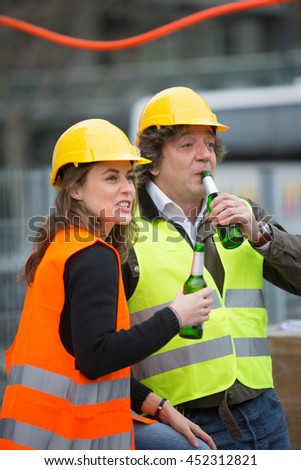 Cheerful male and female team on construction site having a beer after work.  Selective focus.