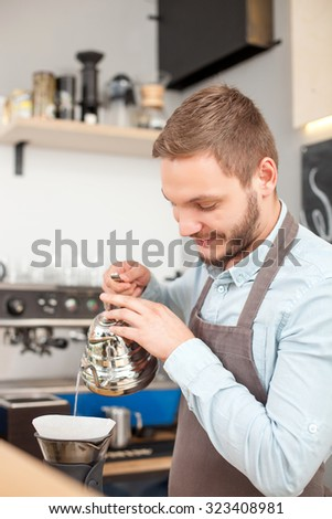 Cheerful male barista is making coffee in cafeteria. He is holding kettle and pouring water into utensil. The man is standing and smiling. He is looking at drink with joy - stock photo