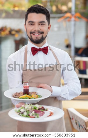 Cheerful male cafe is serving customers. He is standing and holding plate of salad. The man is looking forward and smiling - stock photo
