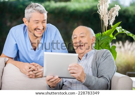 Cheerful male caretaker and senior man using tablet PC at nursing home porch - stock photo