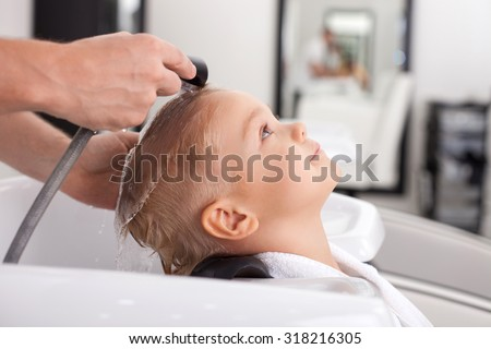 Cheerful male child is having his hair washed in Hair salon. He is leaning his head on sink. The kid is looking up with joy - stock photo