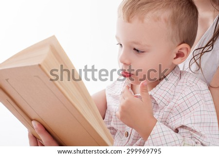 Cheerful male child is sitting on female knee and looking at the book with seriousness. His mother is teaching him the letters. Isolated on background - stock photo