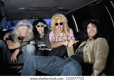 Cheerful male friends sitting in a limousine - stock photo